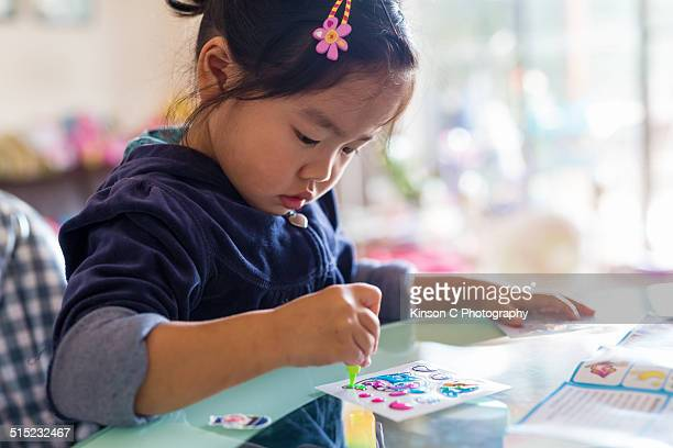Closeup of a young girl creating sticker at home