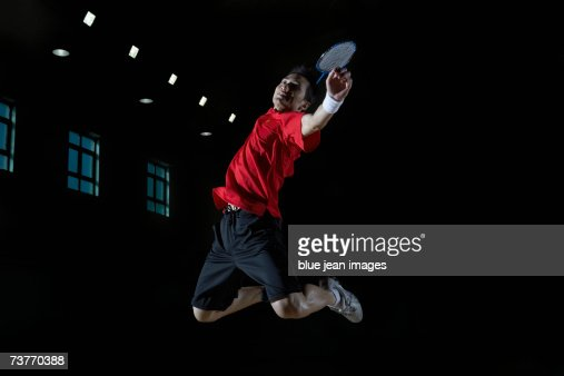 Close-up of a young man as he leaps high in the air and prepares to smash a shuttlecock during a game of badminton.