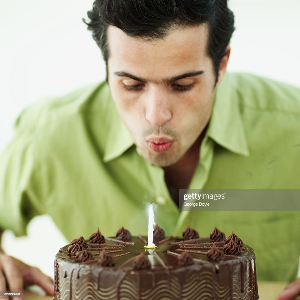 Closeup Of A Young Man Blowing Out A Candle On A Birthday Cake
