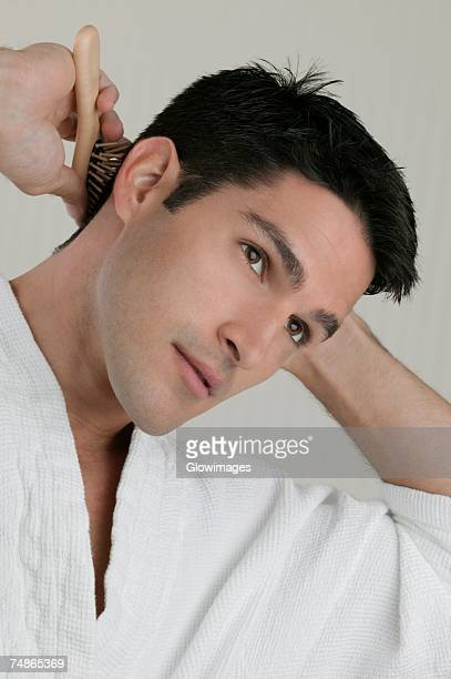 Close-up of a young man combing his hair