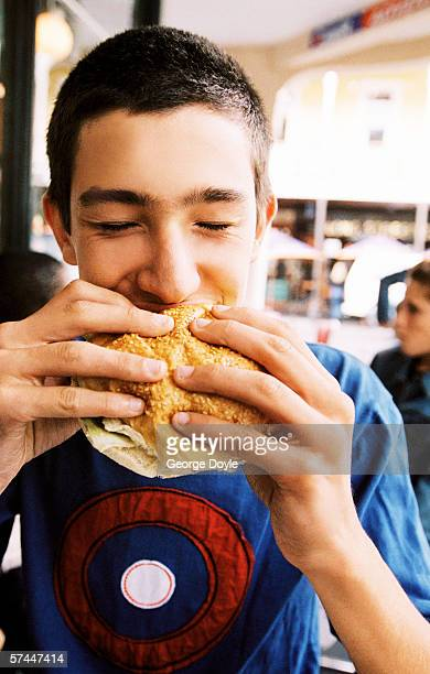 close-up of a young man eating a sandwich in a caf+?