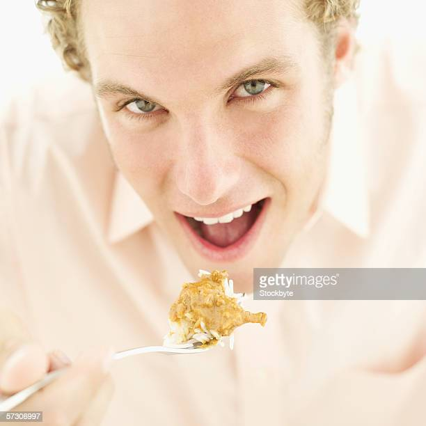Close-up of a young man eating rice and curry with a fork