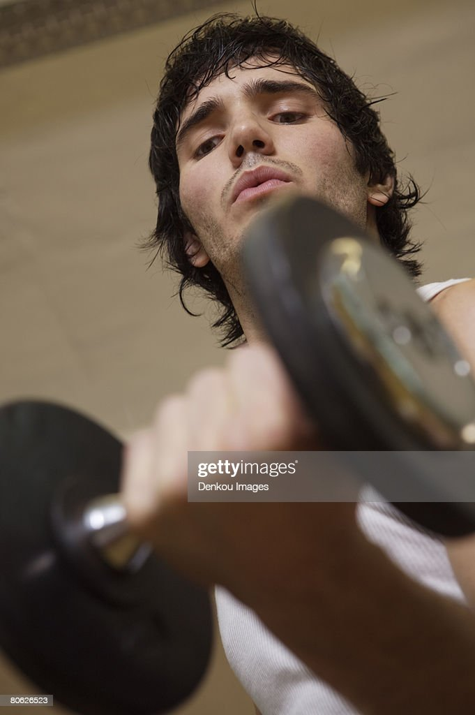 Close-up of a young man exercising with a dumbbell : Stock Photo