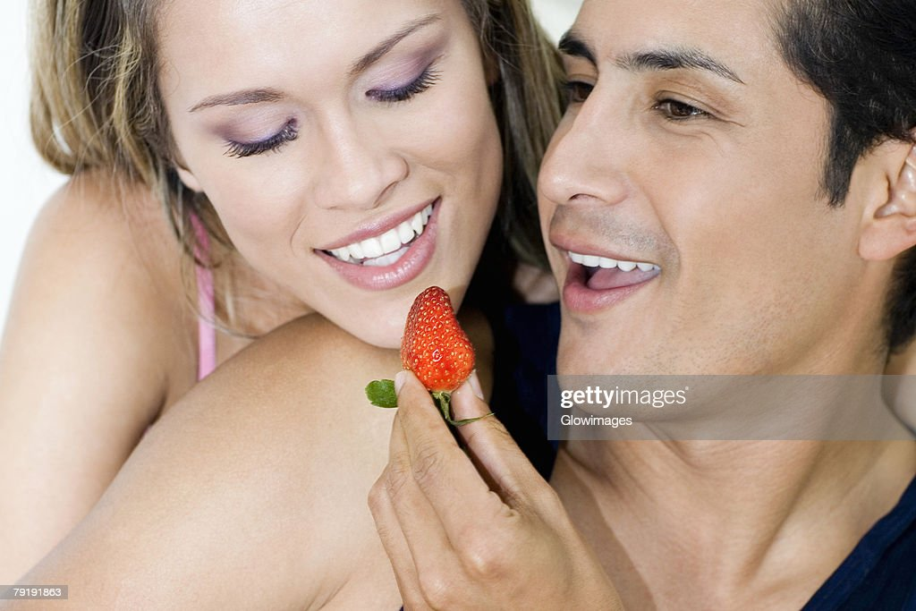 Close-up of a young man feeding a strawberry to a young woman : Stock Photo