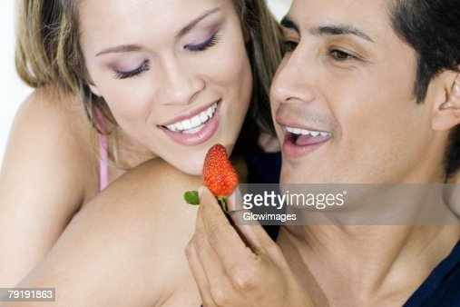 Close-up of a young man feeding a strawberry to a young woman : Foto de stock
