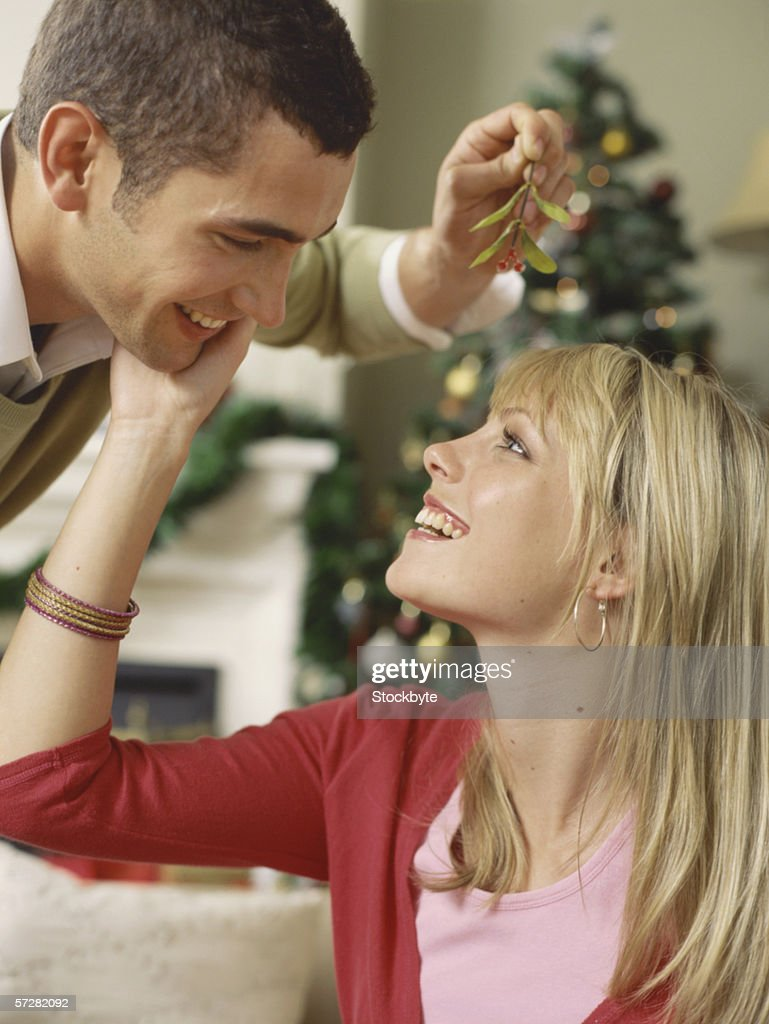 Close-up of a young man holding mistletoe and looking at a young woman and smiling
