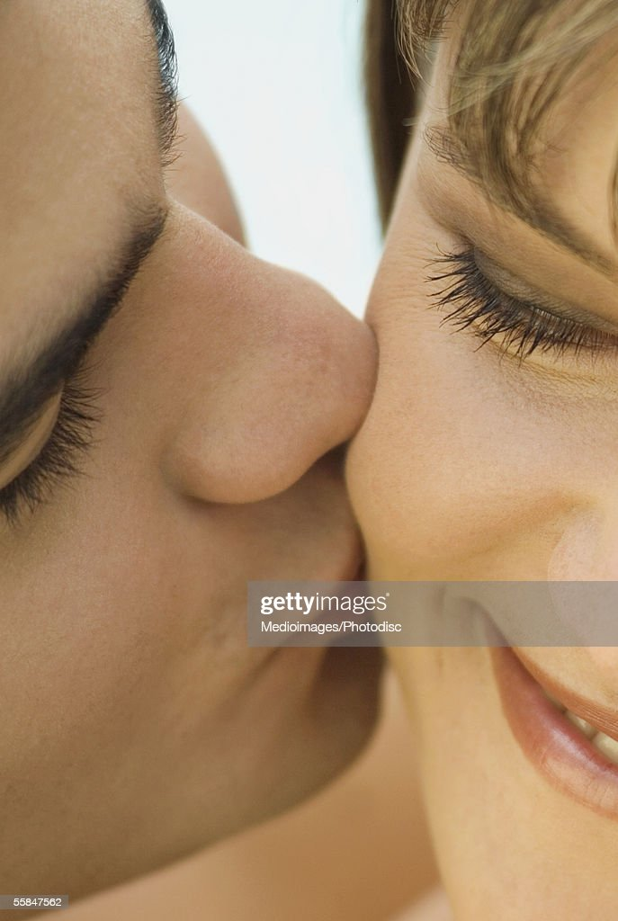Close-up of a young man kissing a young woman : Stock Photo