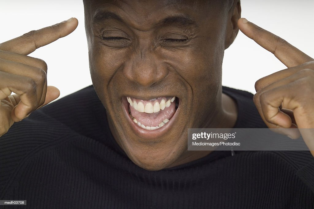 Close-up of a young man laughing and pointing at himself : Stock Photo