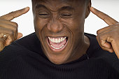 Close-up of a young man laughing and pointing at himself