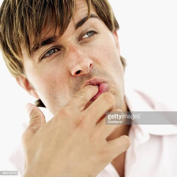 close-up of a young man licking his finger