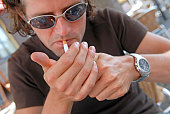Close-up of a young man lighting a cigarette