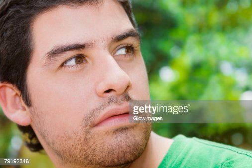 Close-up of a young man looking away : Foto de stock