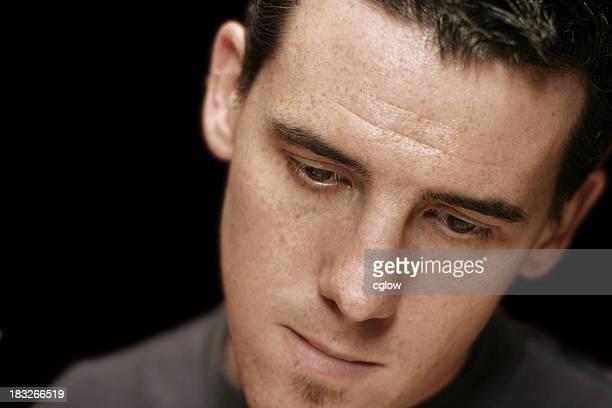 A closeup of a young man looking sad
