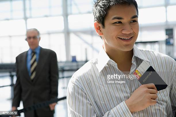 Close-up of a young man putting a passport with an airplane ticket in his shirt's pocket