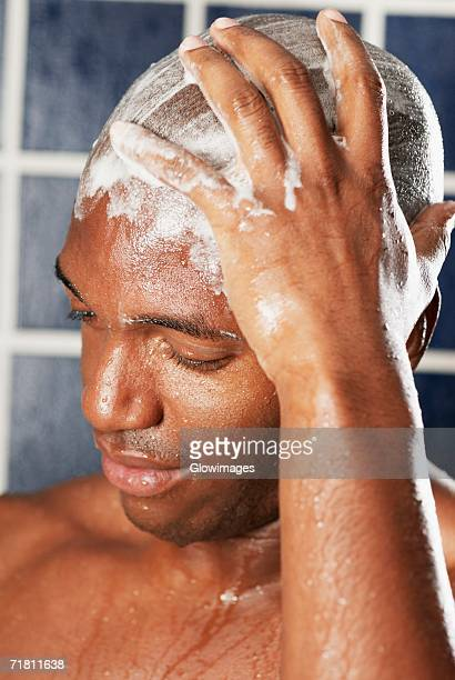Close-up of a young man scrubbing his head