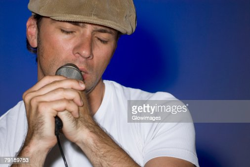 Close-up of a young man singing into a microphone : Foto de stock