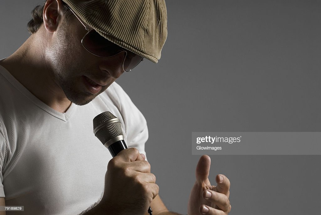 Close-up of a young man singing into a microphone : Stock Photo