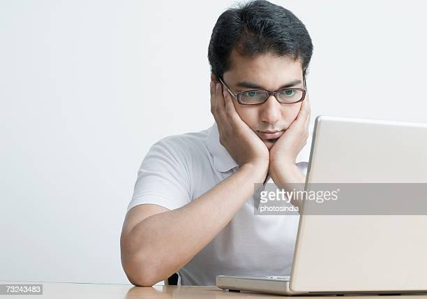 Close-up of a young man sitting in front of a laptop with his head in his hands