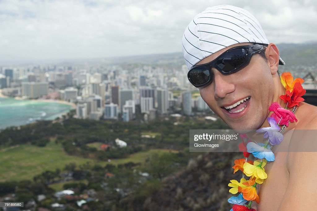 Close-up of a young man smiling, Diamond Head, Waikiki Beach, Honolulu, Oahu, Hawaii Islands, USA : Stock Photo