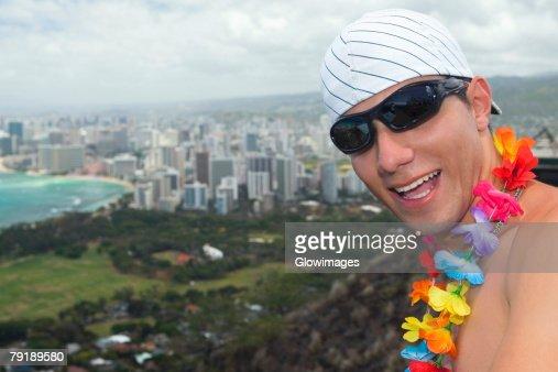 Close-up of a young man smiling, Diamond Head, Waikiki Beach, Honolulu, Oahu, Hawaii Islands, USA : Stock Photo