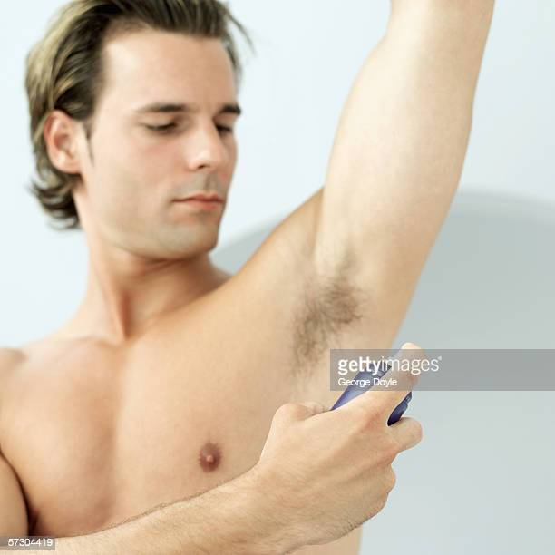 Close-up of a young man spraying deodorant under his arm