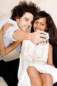 Close-up of a young man taking a picture of himself and a young woman with a mobile phone