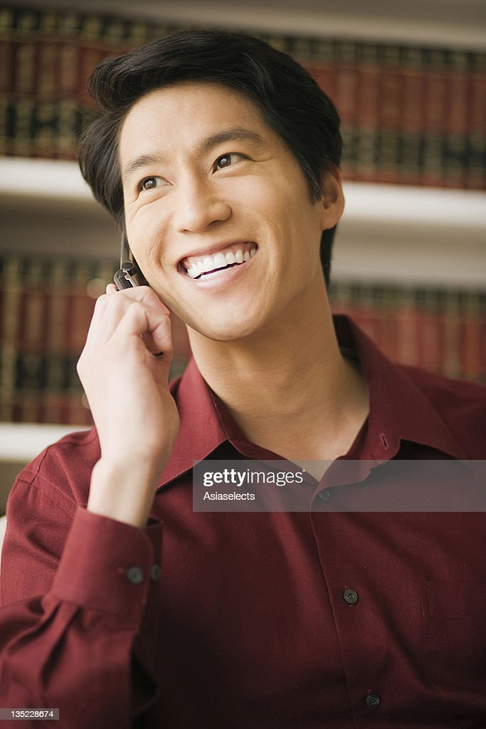 Close-up of a young man talking on a mobile phone and smiling : Stock Photo