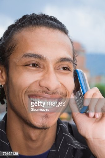 Close-up of a young man talking on a mobile phone : Foto de stock