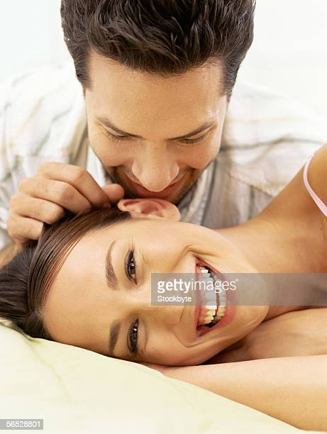 close-up of a young man whispering into a young woman's ear