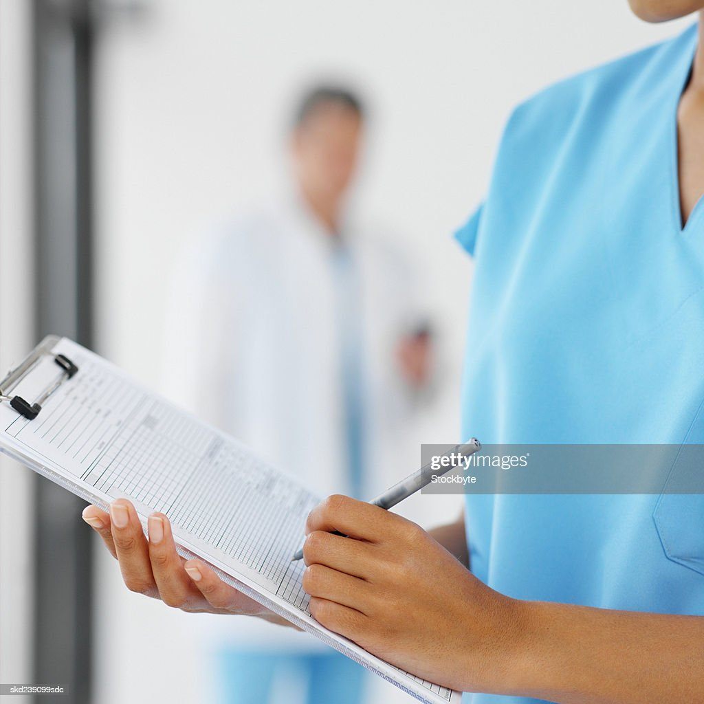 Close-up of a young surgeon holding clipboard with colleague in background : Stock Photo