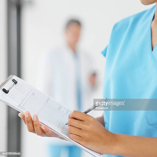 Close-up of a young surgeon holding clipboard with colleague in background
