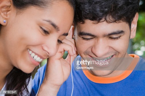 Close-up of a young woman and a mid adult man listening to music and smiling : Foto de stock