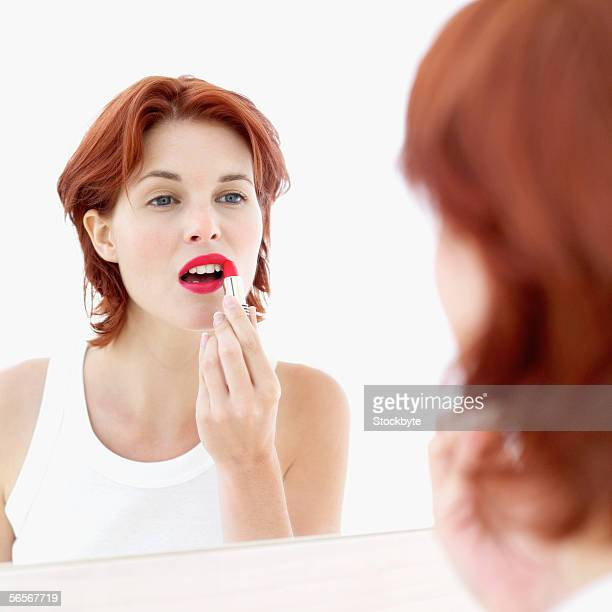 close-up of a young woman applying lipstick