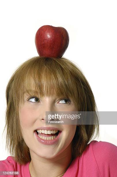 Close-up of a young woman balancing an apple on her head