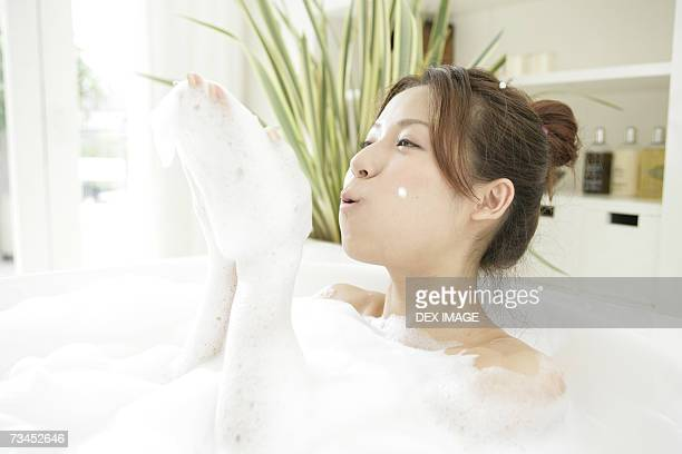 Close-up of a young woman blowing foam in a bubble bath