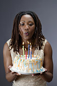 Close-up of a young woman blowing out candles on a birthday cake