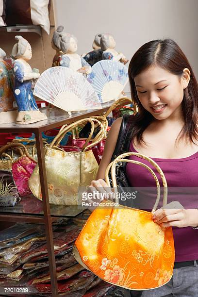 Close-up of a young woman choosing a hand bag