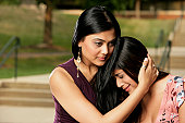 Close-up of a young woman consoling her friend