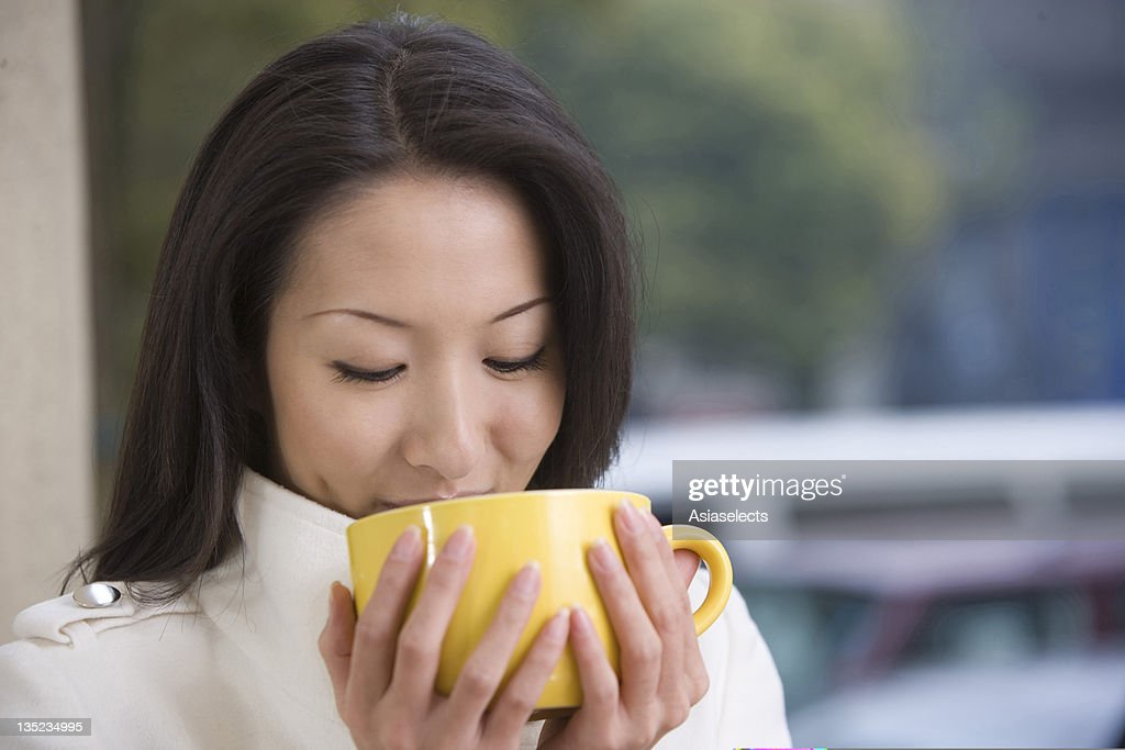 Close-up of a young woman drinking coffee : Stock Photo