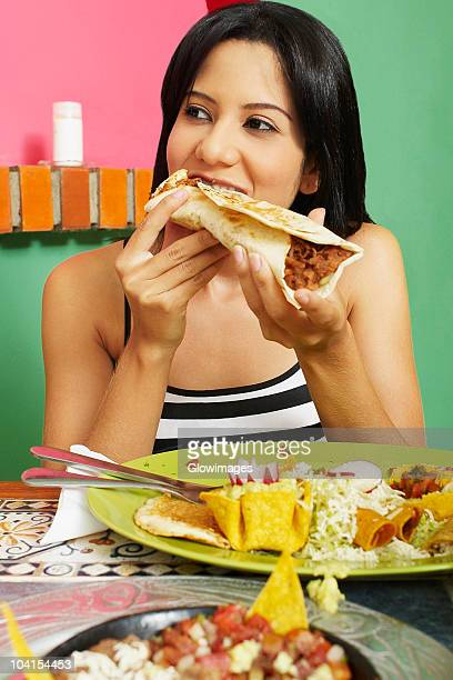 Close-up of a young woman eating a wrap sandwich