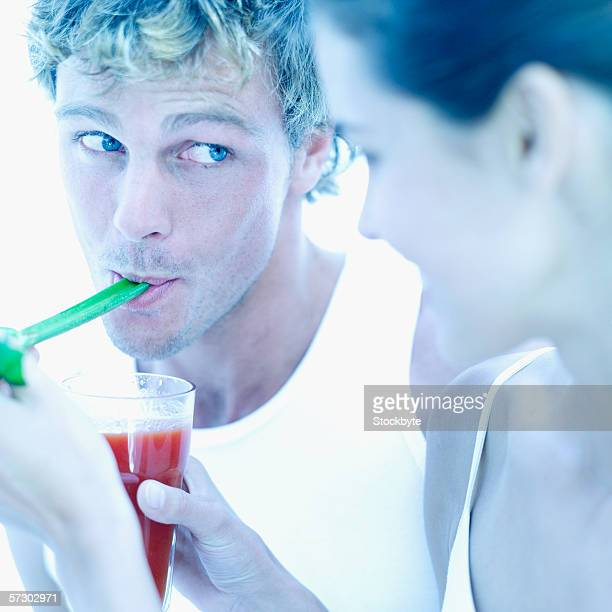Close-up of a young woman feeding a young man a celery stick