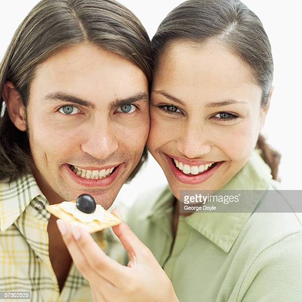 Close-up of a young woman feeding a young man a cracker with cheese