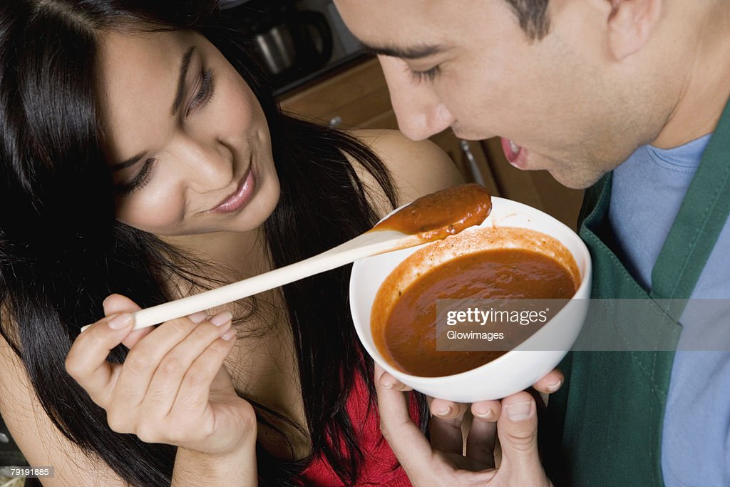 Close-up of a young woman feeding tomato soup to a mid adult man in the kitchen : Stock Photo