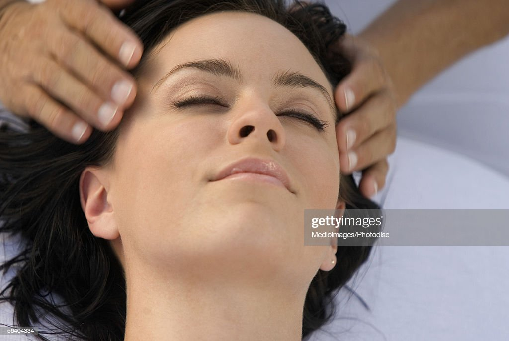 Close-up of a young woman getting a head massage : Stock Photo
