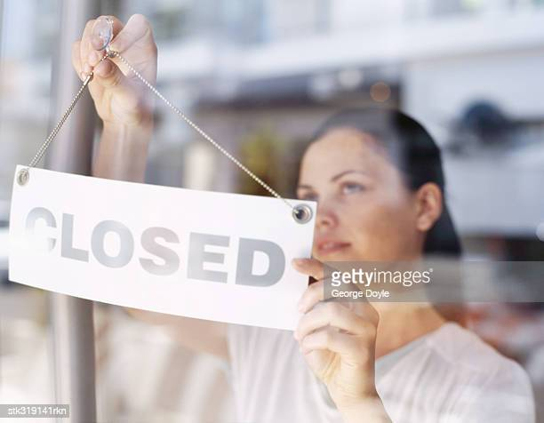 close-up of a young woman hanging closed sign on a glass door