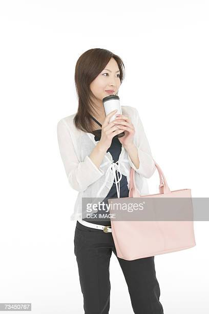 Close-up of a young woman holding a bottle and a purse
