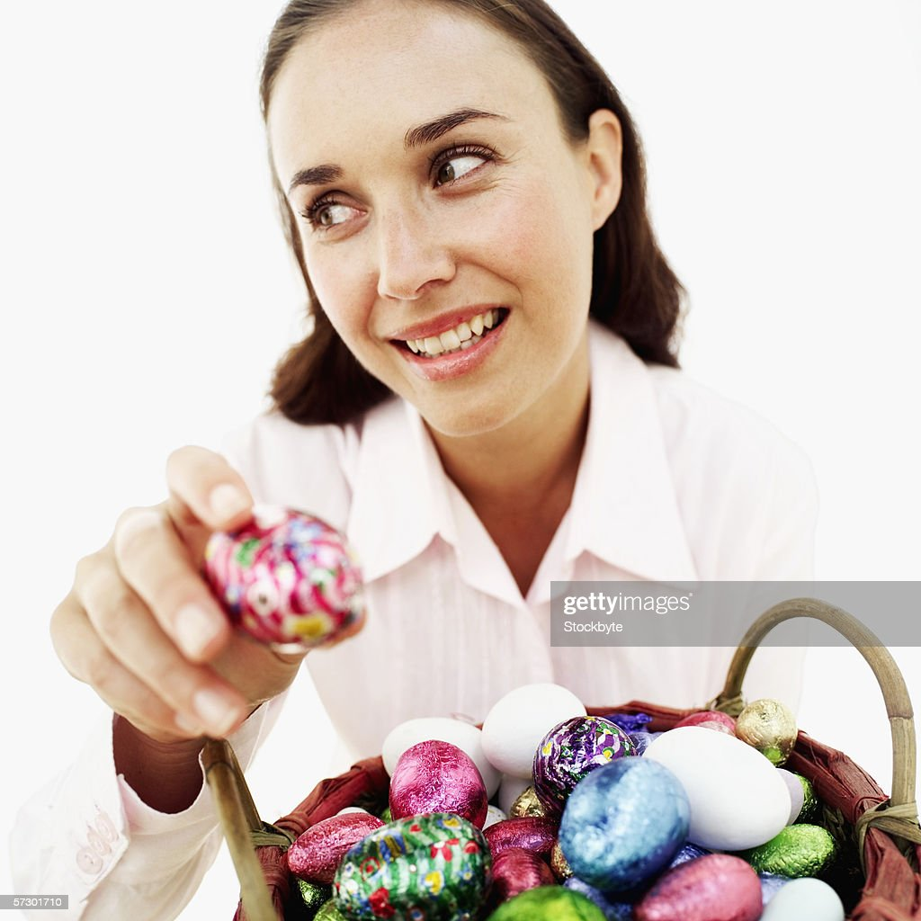 Close-up of a young woman holding a foil wrapped Easter egg : Stock Photo