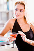 Close-up of a young woman holding a glass of martini