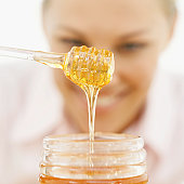 close-up of a young woman holding a honey dipper