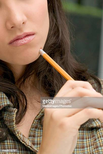 Close-up of a young woman holding a pencil